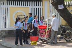 在断裂期间,越南女小学生买从摊贩的食物 颜色,越南 免版税库存照片