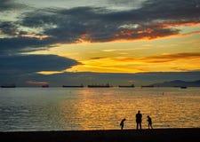 在斯坦利海滩温哥华加拿大,在前景的3 silhuettes的日落 免版税库存照片