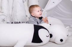 在斯堪的纳维亚样式的新年,圣诞树,有孩子的妈妈,儿童` s玩具,睡眠婴孩 免版税图库摄影