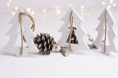 在斯堪的纳维亚样式的白色圣诞节装饰与木冷杉treeas和杉木锥体, bokeh在背景中点燃 免版税库存照片