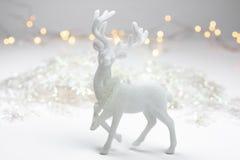 在斯堪的纳维亚样式的白色圣诞节装饰与驯鹿、雪剥落和bokeh在背景中点燃 库存图片