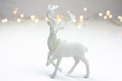 在斯堪的纳维亚样式的白色圣诞节装饰与驯鹿和bokeh在背景中点燃 库存照片