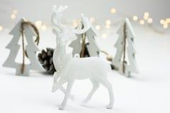 在斯堪的纳维亚样式的白色圣诞节装饰与驯鹿,木冷杉treeas和杉木锥体, bokeh在背景中点燃 免版税库存照片