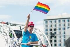 在斯德哥尔摩骄傲游行期间,供以人员拿着在他的头的彩虹旗子 库存照片
