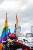 在斯德哥尔摩骄傲游行期间,妇女在有彩虹的军用样式骑马摩托车穿戴了 图库摄影