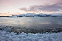 在斯瓦尔巴特群岛,挪威的白色多雪的山 冰在海洋,微明 免版税库存图片