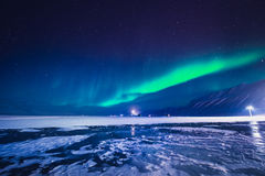 在斯瓦尔巴特群岛,朗伊尔城,卑尔根群岛,挪威墙纸山的北极光  免版税图库摄影