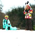在斯诺伊小山顶部的两个女孩微笑 图库摄影