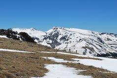 在斯诺伊山峰上面的现出轮廓的远足者 库存照片
