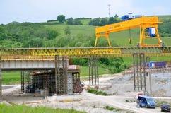 在斯洛伐克D1高速公路建造场所的黄色桥式起重机  除了起重机有有些工作者和汽车 免版税图库摄影