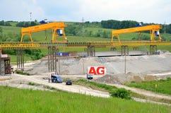 在斯洛伐克D1高速公路建造场所的黄色桥式起重机  除了起重机有有些工作者和汽车 库存图片
