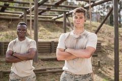 在新兵训练所的障碍桩期间站立与胳膊的军人横渡了 库存照片