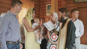 在新出生的教母和母亲打击在婴儿洗礼仪式期间 股票录像