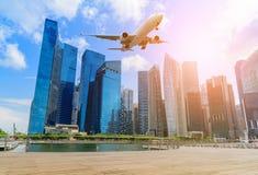 在新加坡商业区上市地平线的平面飞行  免版税库存照片
