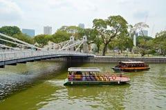 在新加坡河的巡航小船 免版税库存图片