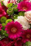 在新娘五颜六色的花束的两个婚戒 库存图片