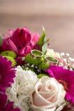 在新娘五颜六色的花束的花的两个婚戒 免版税库存照片