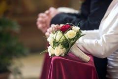 在新娘和新郎前面的新娘花束 库存照片