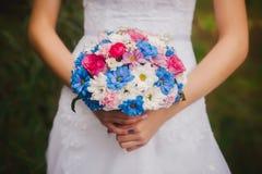 在新娘和新郎手的美丽的婚礼花束在公园背景 婚姻花束的白色和蓝色雏菊 图库摄影