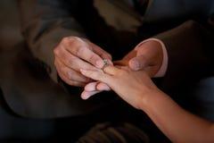 在新娘手指的婚戒 免版税库存图片