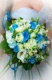 在新娘的手上婚姻蓝色和白花在婚礼之日 库存图片