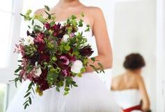 在新娘的手的婚礼花束 免版税库存图片