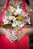 在新娘的手的婚礼花束 库存照片