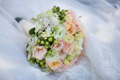 在新娘的礼服的婚礼花束 免版税库存照片