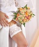 在新娘的腿的袜带。 免版税库存照片