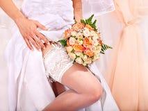 在新娘的腿的袜带。 免版税库存图片