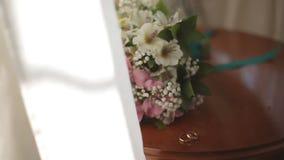 在新娘的花束的背景的婚戒 股票录像