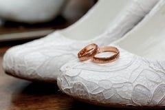 在新娘的鞋子的婚戒 免版税库存图片