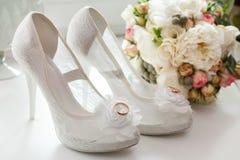 在新娘的鞋子的婚戒 图库摄影