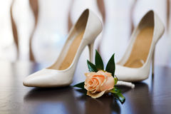 在新娘的鞋子的背景的新郎的钮扣眼上插的花 免版税库存图片