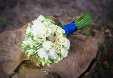 在新娘花束的婚姻的金黄圆环 免版税图库摄影