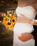 在新娘婴孩爆沸和拿着向日葵花束附近被包裹的新娘和新郎手 免版税图库摄影