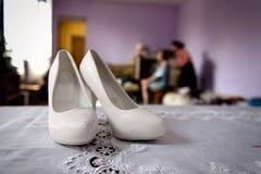 在新娘` s室关闭的白色婚礼鞋子 库存照片
