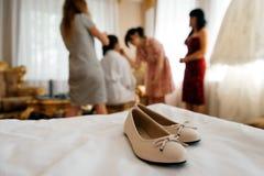 在新娘` s室关闭的米黄婚礼鞋子 免版税库存照片