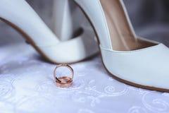 在新娘` s白色鞋子的美好的婚戒 免版税库存图片