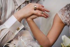 在新婚佳偶的时髦的手上的婚戒 免版税库存照片
