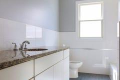 在新建工程家黑暗的木细木家具的主浴室 免版税库存图片
