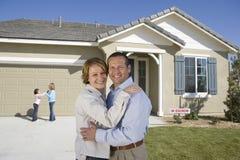 在新房前面的愉快的家庭 免版税库存图片