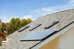 在新房屋顶的太阳水嵌入式供暖器有反对蓝天的天窗的 免版税库存照片