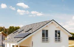 在新房屋顶的太阳水嵌入式供暖器有反对蓝天的天窗的 免版税图库摄影