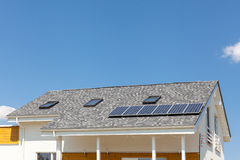 在新房屋顶的太阳水嵌入式供暖器有反对蓝天的天窗的 库存照片