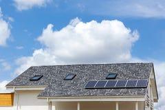 在新房屋顶的太阳水嵌入式供暖器有反对蓝天的天窗的 免版税库存图片