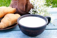 在新月形面包和白花旁边在水罐附近是一个杯子牛奶 免版税库存图片