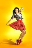 在新橙色背景的现代样式女孩跳舞 Hip Hop减速火箭的舞蹈家 库存图片