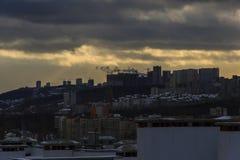 在新的住宅区的建筑用起重机 晴朗的阴天 太阳射线通过重的云彩 免版税图库摄影