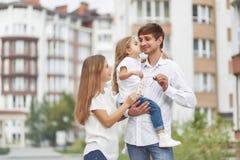 在新的公寓前面的愉快的家庭 免版税库存照片